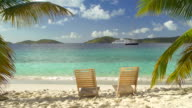 video of two empty teak chairs at a Caribbean beach video