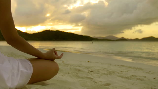 video of woman practicing yoga during sunset at the beach video