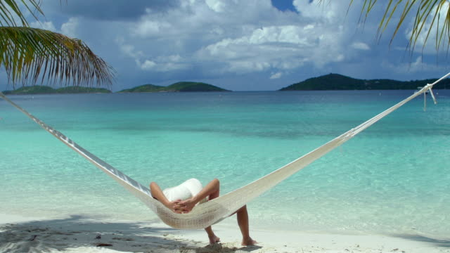 video of woman relaxing in hammock at a beach video