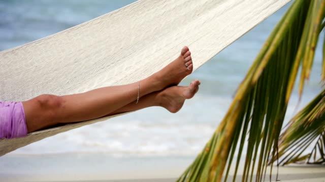 video of woman sunbathing in hammock at a Caribbean beach video
