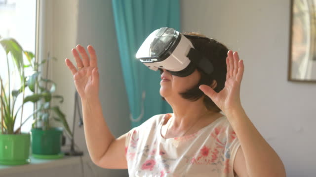 Video of woman wearing virtual reality glasses and playing games at home in slow motion in 4k video