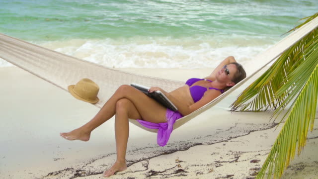 video of woman with laptop in hammock at a beach video