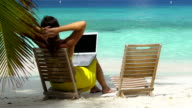 video of woman working on laptop at a Caribbean beach video