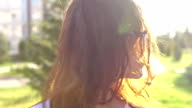 Video portrait teenage girl wearing glasses walking in the park shaking hair video