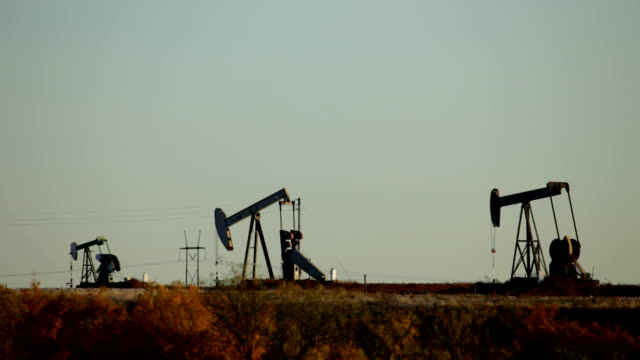 HD video silhouetted oil rigs pump in Texas fields video
