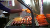 Video vendors grilling Taiwanese bbq sausages both red and white. Delicious must try food of Taiwan video
