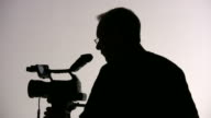 (HD1080i) Videographer Cameraman Adjusts Camera, Directs; Silhouette video
