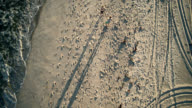View directly above to young man and teenager girl who are standing and talking on the beach. Aerial footage. Focus on shadows and sandy surface. video