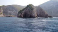 View from a boat at the Greek shore covered with rocks. video