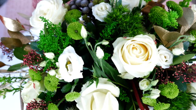 view from above, close-up, the floral composition consists of eucalyptus, solidago, Rose of avalanche, Santini , Eustoma, Brunia green, Barbatus. Flower bouquet, rotation on white background video