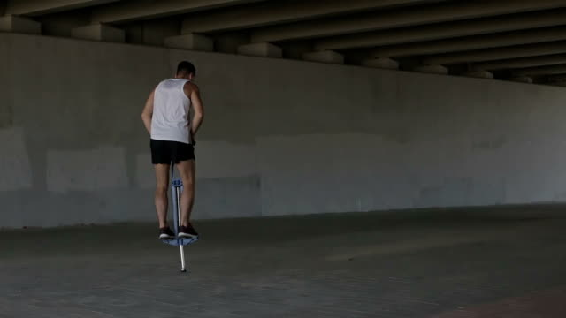 View from the back. Sports guy in a shirt and shorts jumping on the spring device under a bridge video