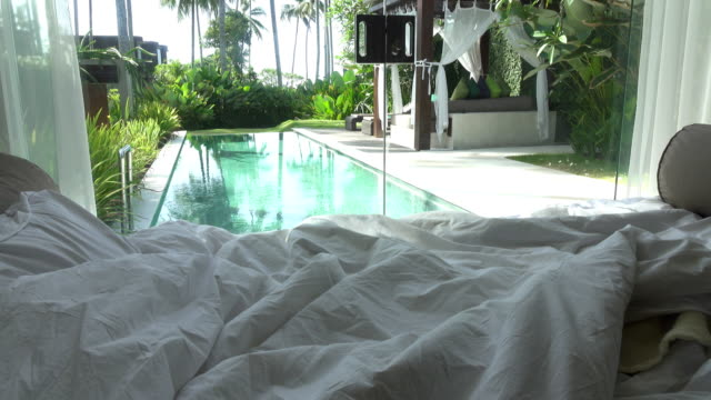 View from the bedroom on pool and a tropical garden with palm trees video