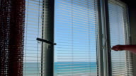 View from the open window with blinds on the sea in summer video