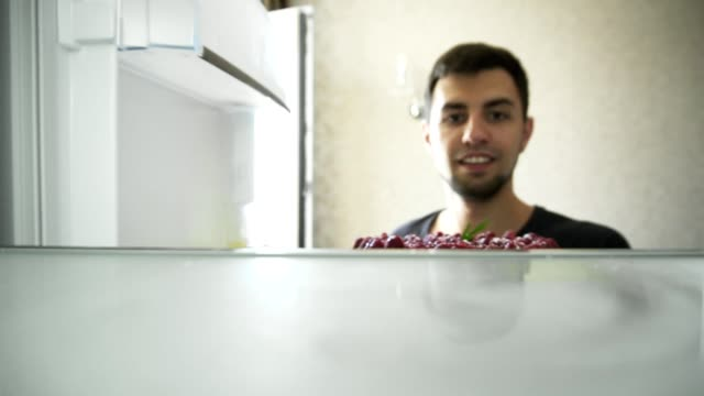 View from the refrigerator: Young man opens the fridge and puts in the cake decorated with raspberries video