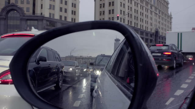View in car's rearview mirror on the city street. video
