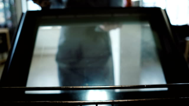 View inside the oven. Young woman open the oven and puts on the baking dish with dough, cooking the cupcakes video