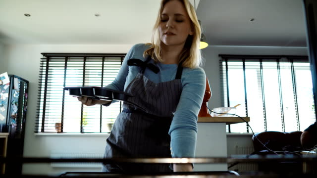 View inside: young beautiful woman opens the oven and puts in the baking tray with cupcakes. Female cooking at home video