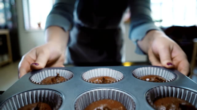 View inside: young woman open oven and putting in baking tray for cupcakes. Female dancing while waiting the desserts video
