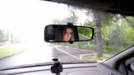 View of a teenager in the car mirror video