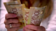 View of a Woman Counting Many Canadian 100 Bills video