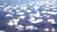 SLOW MOTION: View of arid landscape from airplane high above white clouds video