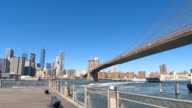 LOW ANGLE VIEW: View of Brooklyn Bridge and Lower Manhattan downtown from pier video