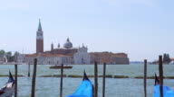 View of church of San Giorgio Maggiore in Venice, Italy with gondolas rocking on water video