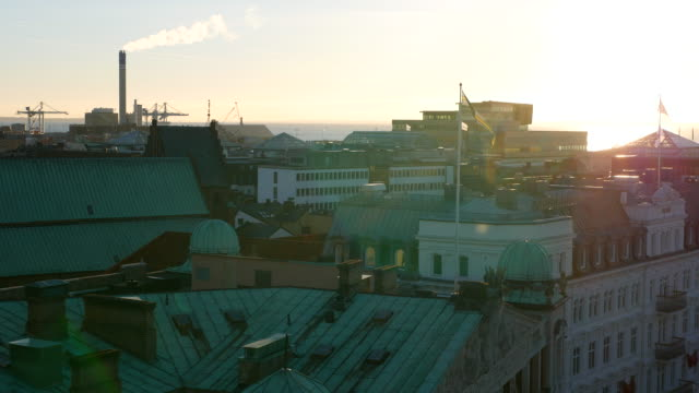 View of city buildings rooftops at sunset. Helsingborg cityscape, Sweden. Smokestack in the background video