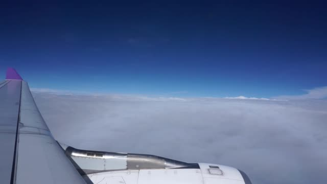 view of cloud and sky from the windows of airplane flying in sunny day at attitude 32000 feets video