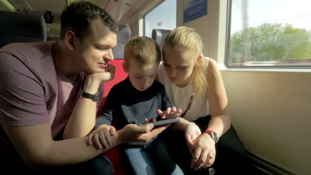 View of happy family in the railway trip using smartphone video