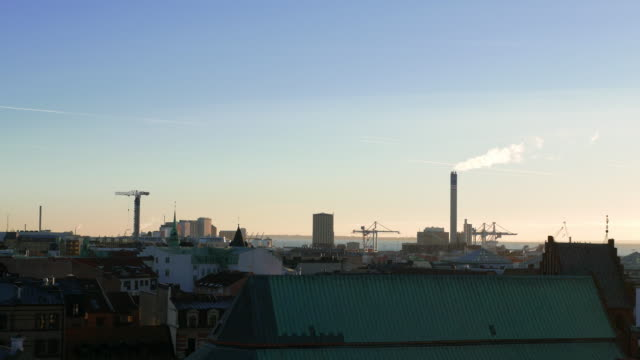 View of industrial district in Helsingborg city at dusk. Smokestack, tower crane and harbor area. Cityscape, Sweden video