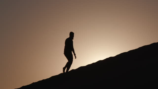 4K view of male tourist in silhouette walking up a sand dune with the rising sun in the background inside the Namib-Naukluft National Park video