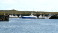 view of moored fishing boats, Atlantic waves are on first plan, tipical icelandic landscape video