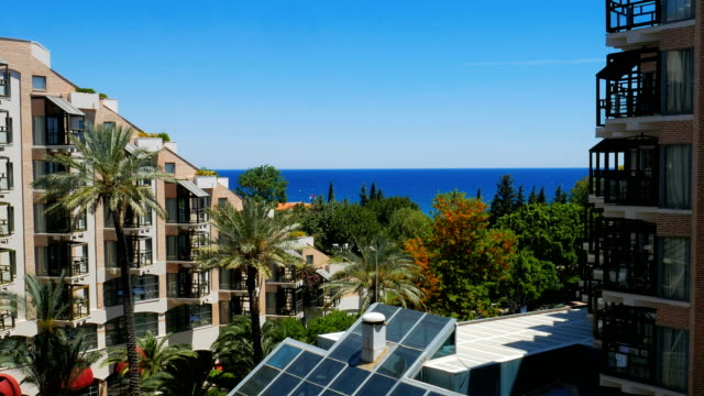 view of sea, palms and building of hotel in summer sunny day, clear blue sky is on background video