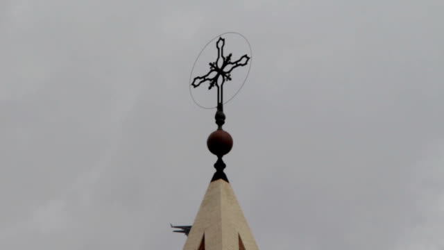 view of the cross of a church with a plane flies over video