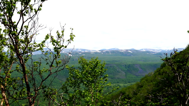 view of the snow-capped mountains and hills in the green valley video