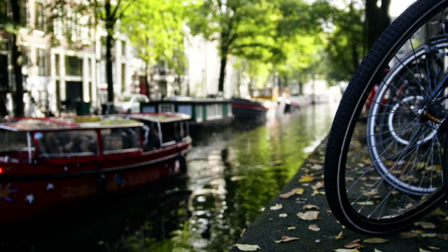 View of wheel of bicycle on the Amsterdam canal, next to floats tour boat, sunny european autumn video