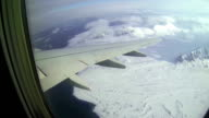 View of wing in the blue sky, the ocean and the snow-capped mountain peaks out from flying airplane. video