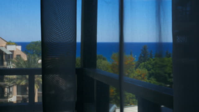 view on seascape from terrace trough white transparent curtain, then curtain is pushed back video