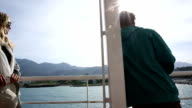 View past man to woman on ferry boat, leaving harbour video