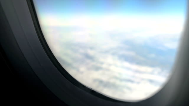 View through window of plane flying above clouds in peaceful sky, air transport video