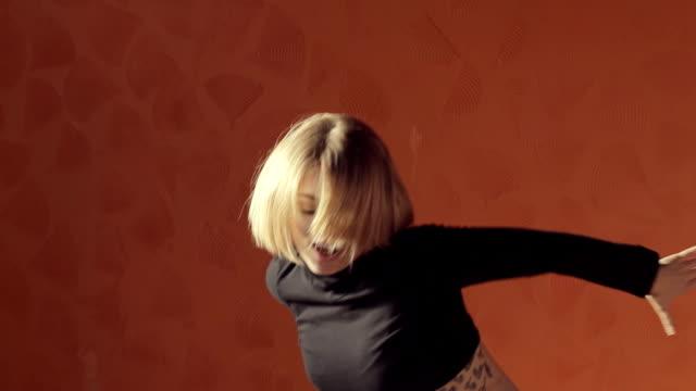 Vigorous blond woman in a short top and tights dancing twerk video