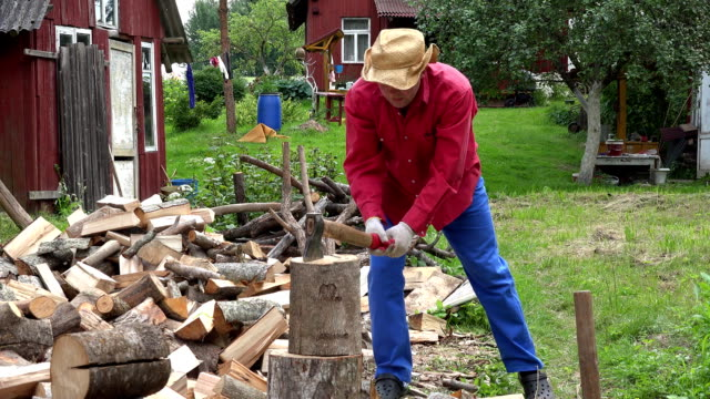 Villager guy with hat unsuccessful try to chop big wood log. FullHD video