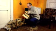 Villager man carry armful of firewood near rural stove video