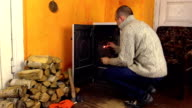 Villager man in sweater light firewood in stove with match video