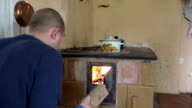 villager man put some firewood in rural kitchen stove video