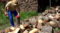 Villager man with old axe chops wood. FullHD video