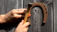 Villager woman hands hammer nails and hang rusty horseshoe symbol of luck on garden house wall. video