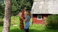 Villager woman hanging laundry on clothesline strings in village. video