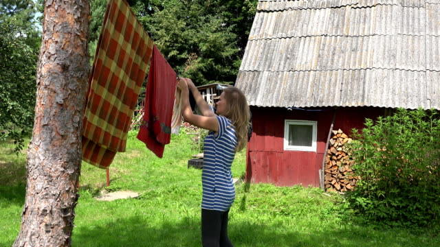 Villager woman hanging washed clothes on clothesline in village. FullHD video